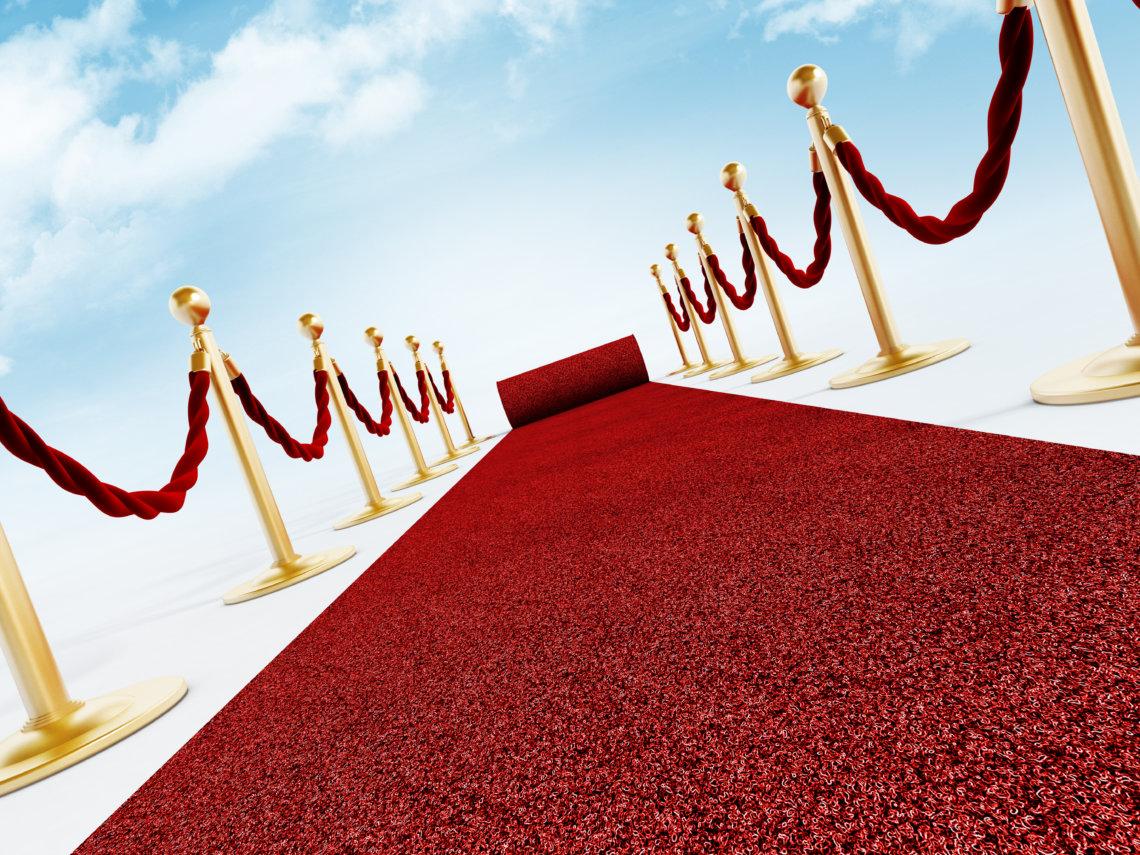 Rolled red carpet and velvet ropes