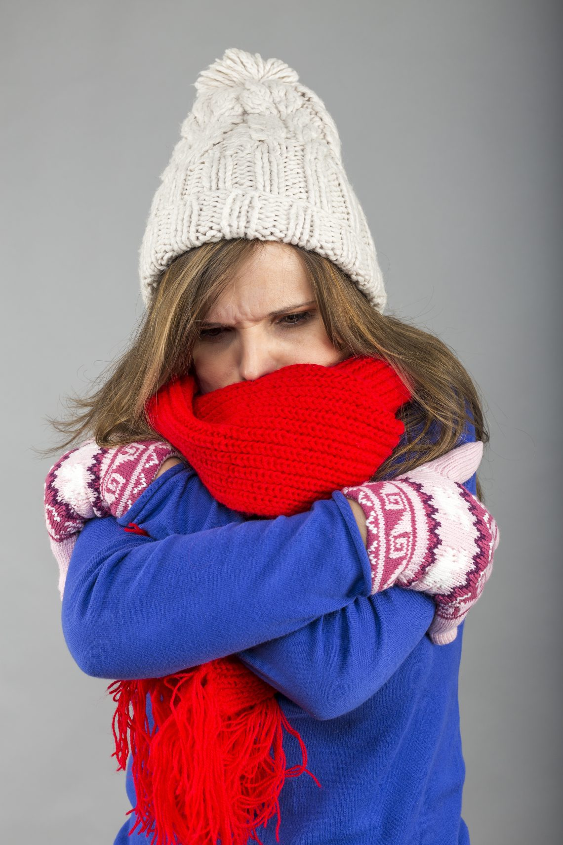 Young woman feeling cold trying to keep warm, shaking and shive