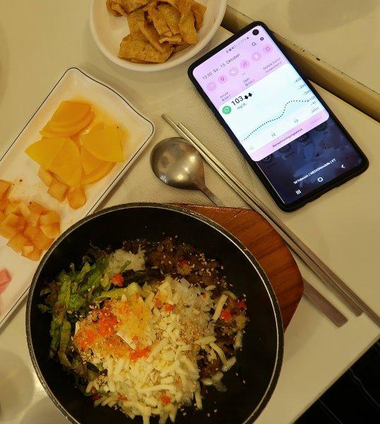 """Koreanisches Essen """"Albab"""", daneben der angezeigte Glukosewert."""