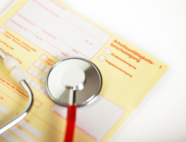 close up of a german paper for the Health insurance In case of illness with a stethoscope