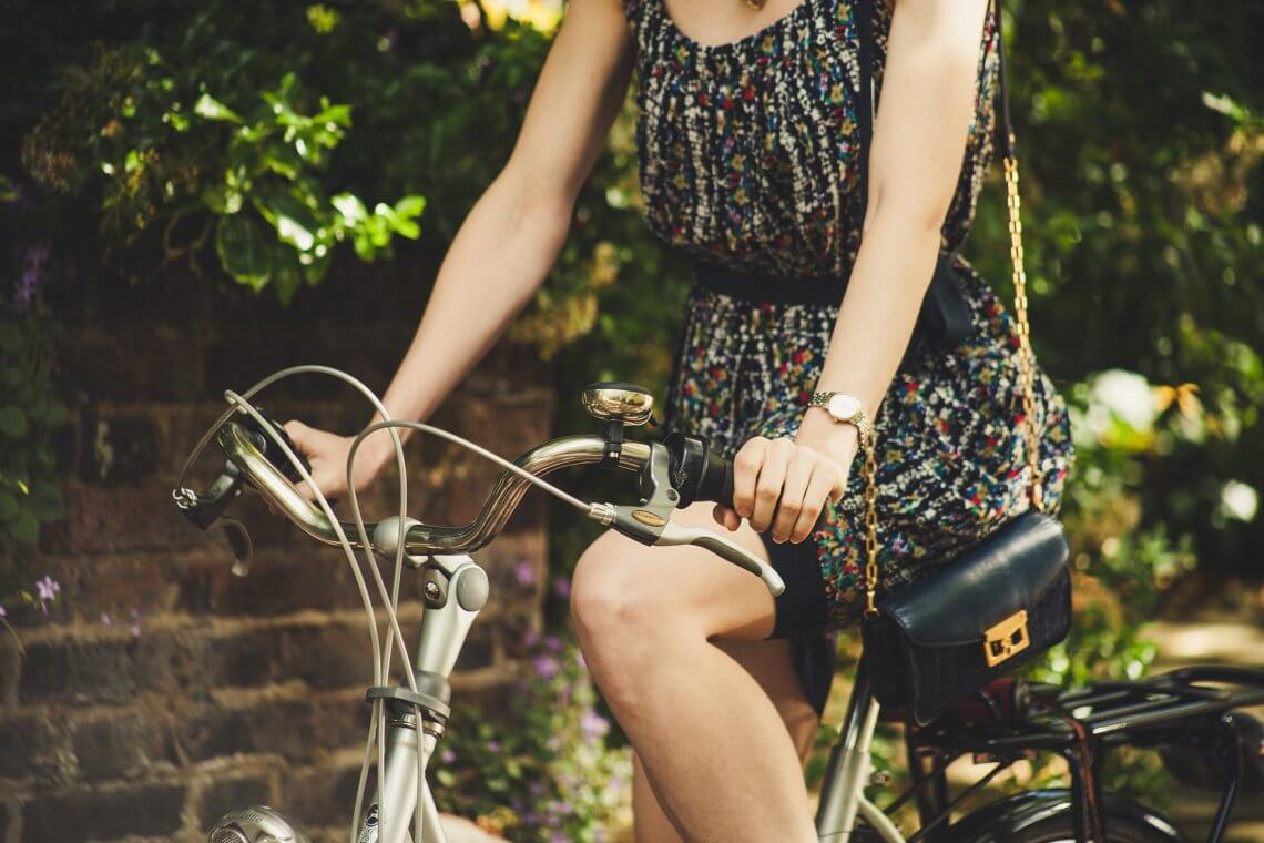 Die Kontaktaufnahme während der Isolation verändert sich / Frau mit kurzem Kleid fährt Fahrrad